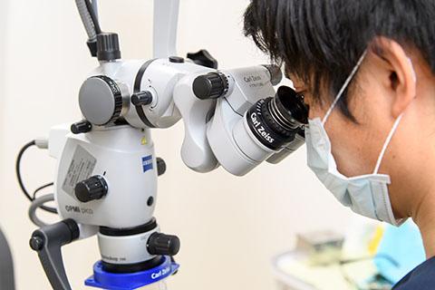 歯科用顕微鏡を覗くドクター
